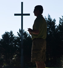 header - parent praying in front of cross